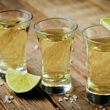 Tequila in glasses with lime and salt on a dark woody background. toning. selective focus